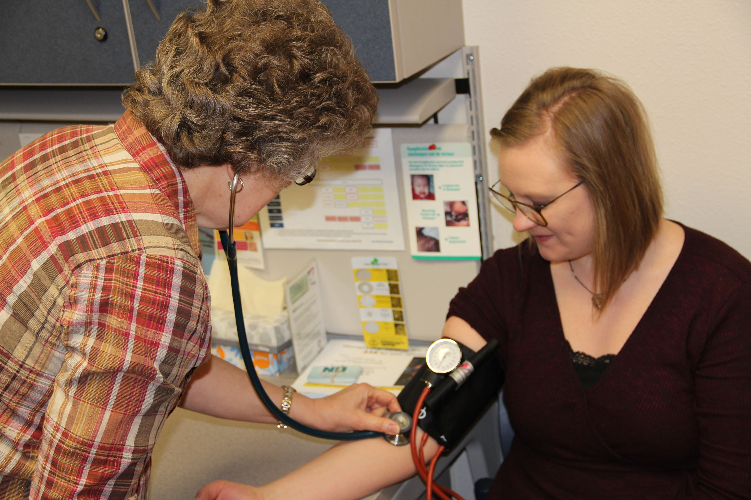 Nurse checking woman's blood pressure JPEG
